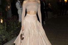 With beige pleated midi skirt, mini bag and beige pumps
