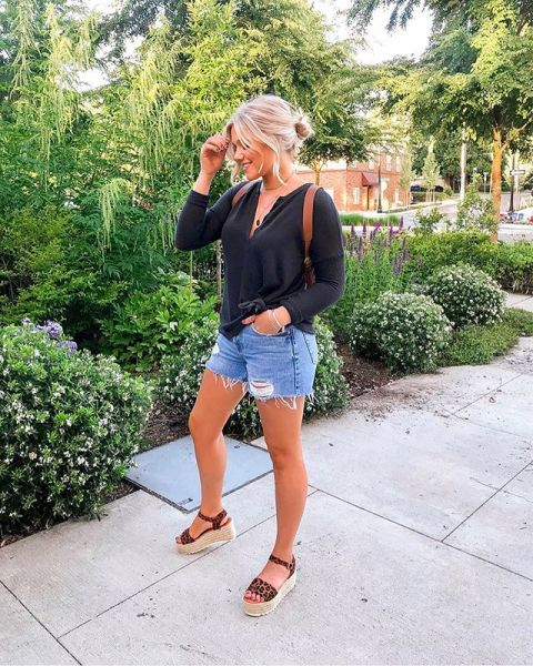 With black loose shirt, brown leather bag and distressed denim shorts