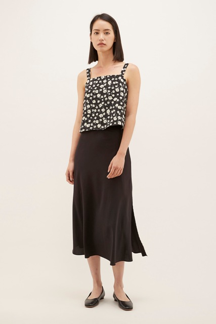 With black midi skirt and black flat shoes