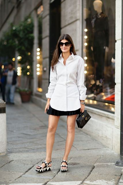 With black pleated skirt, black mini bag and white button down shirt
