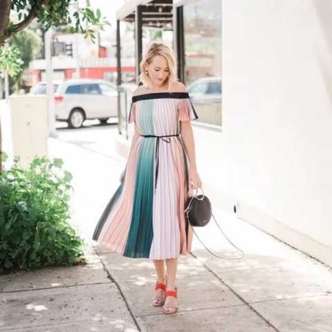 With black rounded bag and red and beige sandals