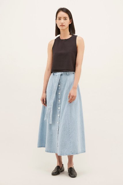 With black sleeveless top and black leather flat shoes
