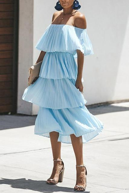 With blue earrings, beige clutch and beige high heels