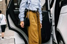 With brown loose trousers, black chain strap bag and black and white low heeled shoes