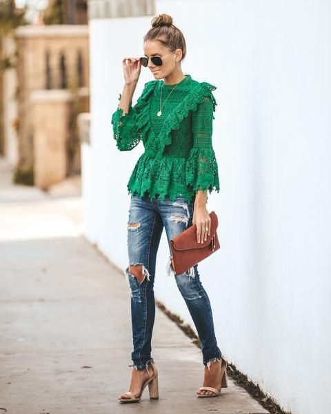 With distressed jeans, brown clutch and beige high heels