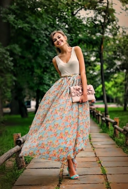 With floral maxi skirt, pale pink clutch and high heels
