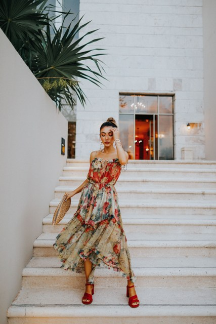 With floral printed pleated asymmetrical dress and red ankle strap sandals