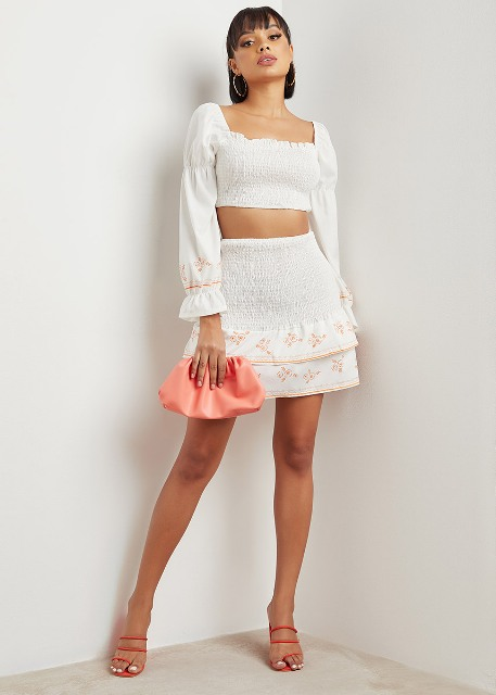 With floral tiered mini skirt, pink clutch and red high heels