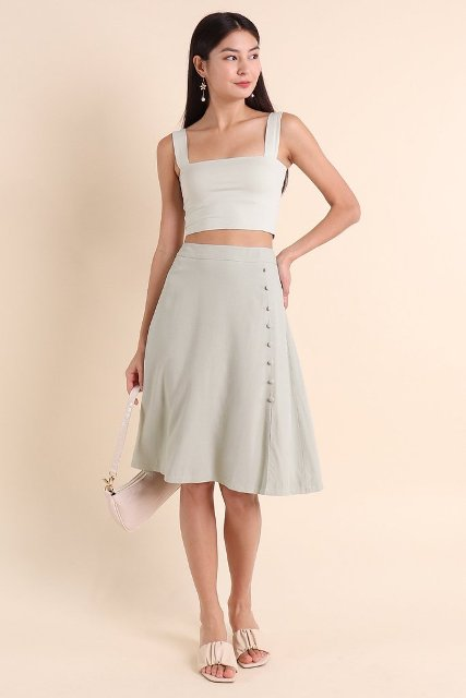 With gray knee length skirt, beige sandals and white bag