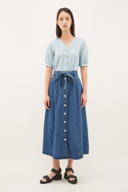 With light blue button down blouse and black flat sandals