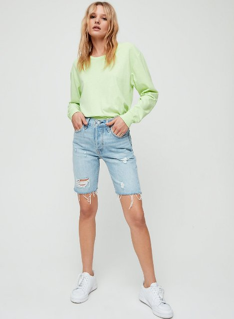 With light green sweatshirt and white sneakers