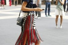 With navy blue shirt, black leather bag and beige lace up high heels