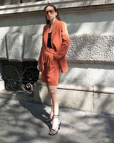 With orange blazer, black top and black ankle strap sandals