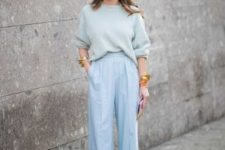With pastel colored loose sweater and sandals