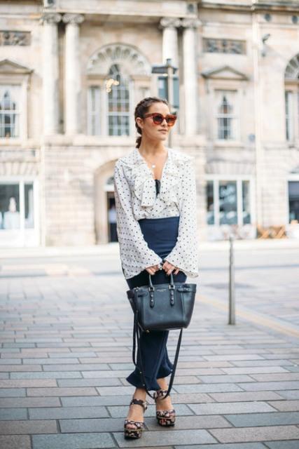 With polka dot ruffled blouse, navy blue midi skirt and black tote bag