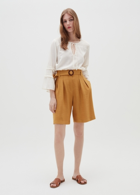 With white bell sleeve blouse and brown flat sandals