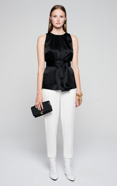 With white cropped trousers, white ankle boots and black clutch