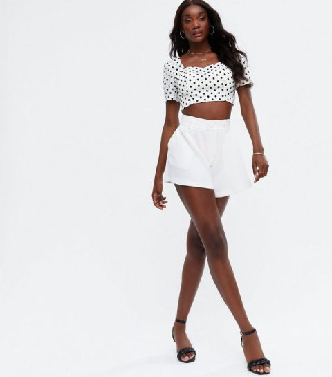 With white high waisted shorts and black ankle strap high heels