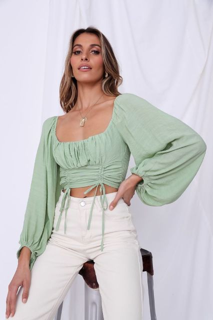 With white high-waisted trousers and necklace