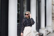 With white knee-length skirt, rounded bag and beige pumps