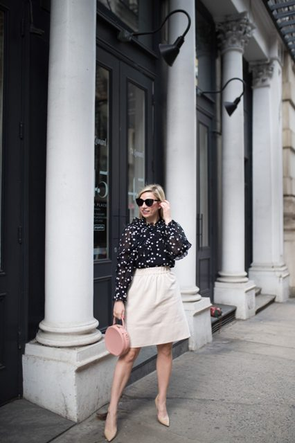 With white knee length skirt, rounded bag and beige pumps