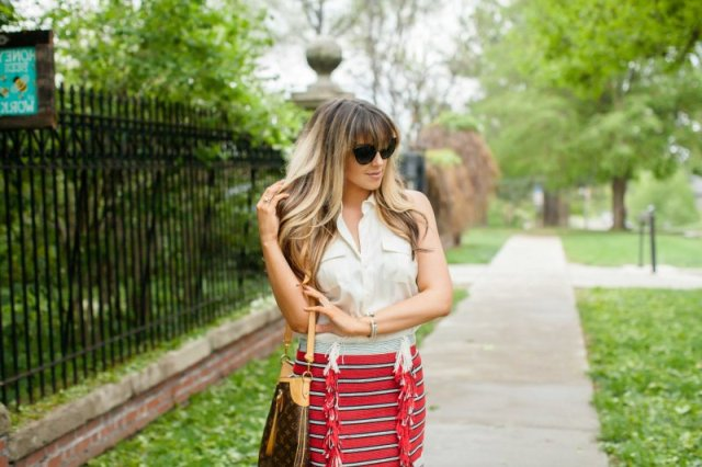 With white sleeveless button down shirt and printed bag