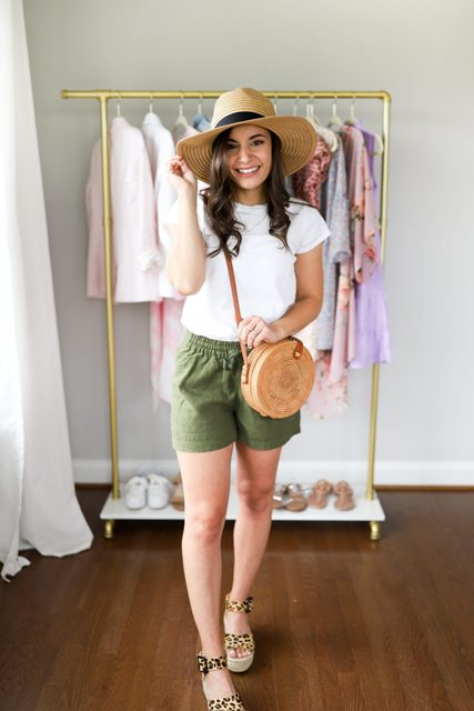 With white t-shirt, wide brim hat, rounded bag and olive green shorts