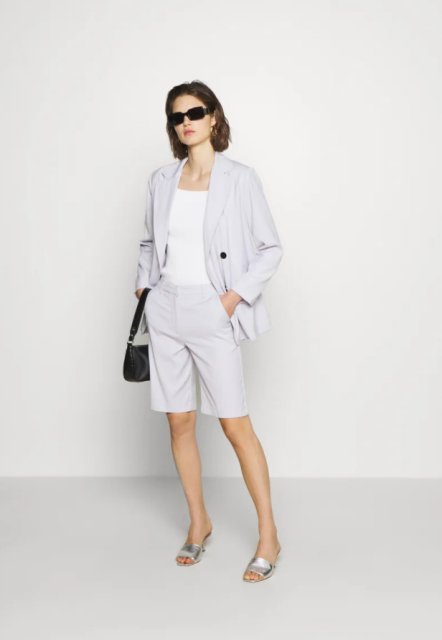 With white top, lilac blazer, black leather bag and silver low heeled mules