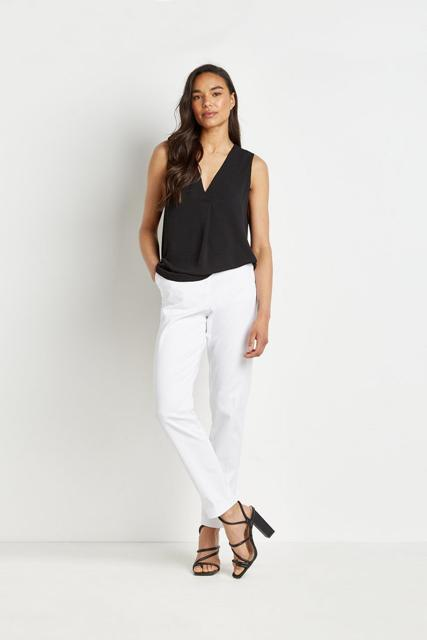 With white trousers and black lace up sandals