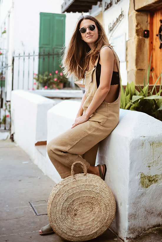 a black crop top, a tan linen overall, grey flats, a round woven bag and classic sunglasses for summer