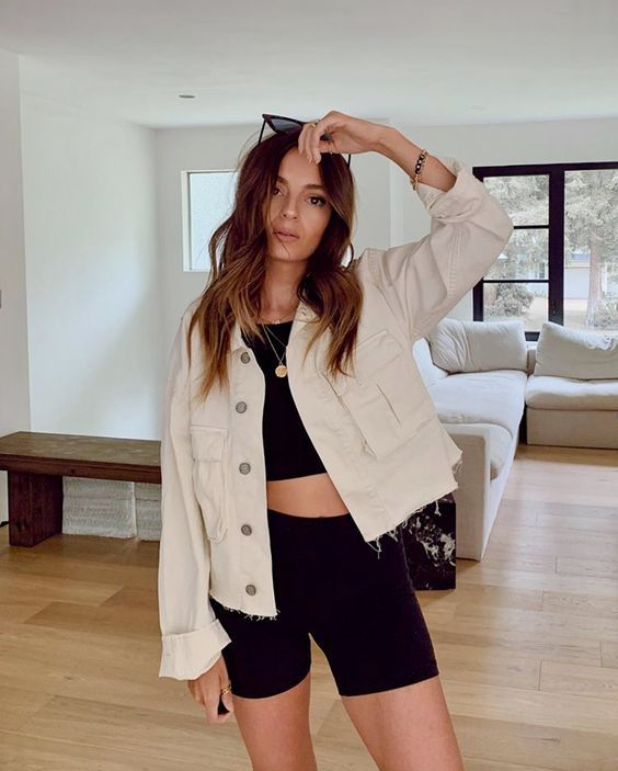 a black crop top and biker shorts, a tan cropped denim jacket and sunglasses