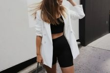 a black crop top and black biker shorts, a white blazer, white trainers and a black bag on chain