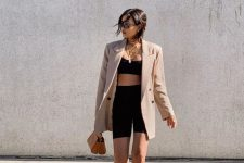 a black crop top, black biker shorts, a tan oversized blazer, nude heels and a tan bag