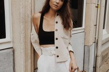a black crop top, white high waisted shorts, a tan jacket and a wooden bag for a casual summer look