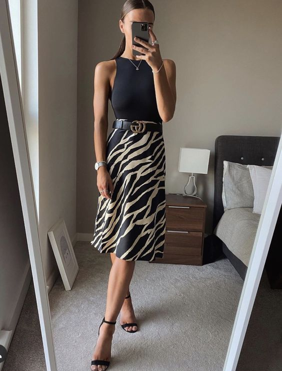 a black halter neckline top, a black printed A-line skirt with a belt, black heels for a sleek and chic look