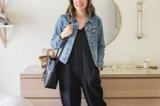 a black jumpsuit, grey birkenstocks, a black bag and a blue denim jacket for a casual work outfit