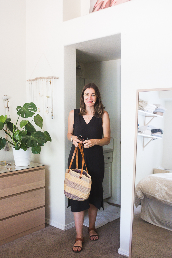 a black linen midi dress with a V-neck and no sleeves, two tone sandals and a striped woven bag for a super hot summer day