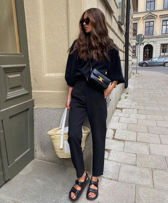 a black long sleeve top, black trousers, black dad sandals and a straw bag for a comfortable summer work look