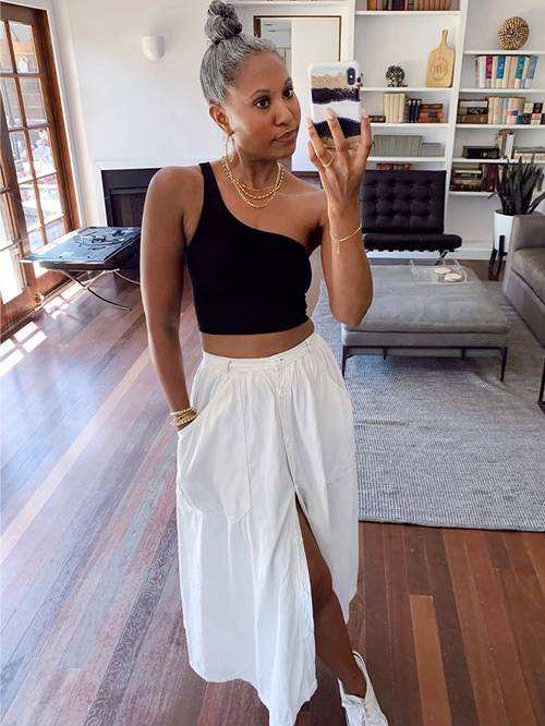 a black one shoulder crop top, a white linen midi skirt, white sneakers and layered necklaces for a lovely look