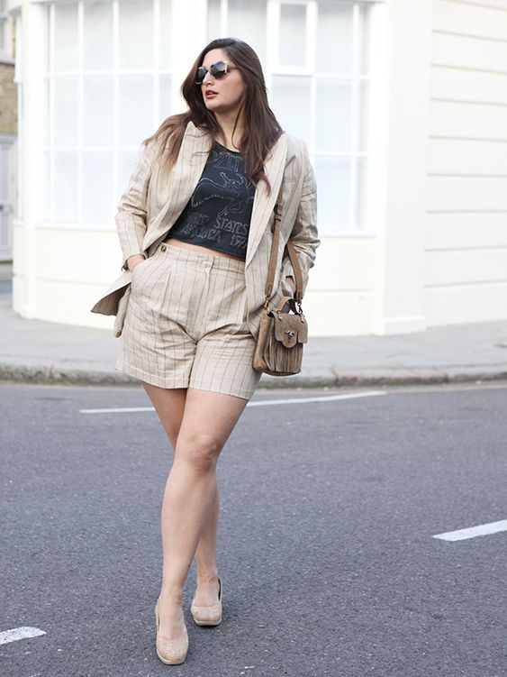 a black printed crop top, a neutral striped short suit, neutral flats and a brown bag