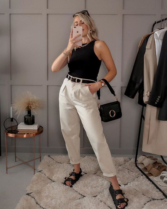 a black sleeveless top, white trousers, a black belt, black dad sandals, a black bag with a ring for a super elegant look