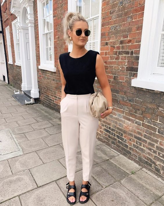 a black sleeveless top with accented shoulders, creamy pants, black dad sandals, a neutral bag for a super chic summer work look