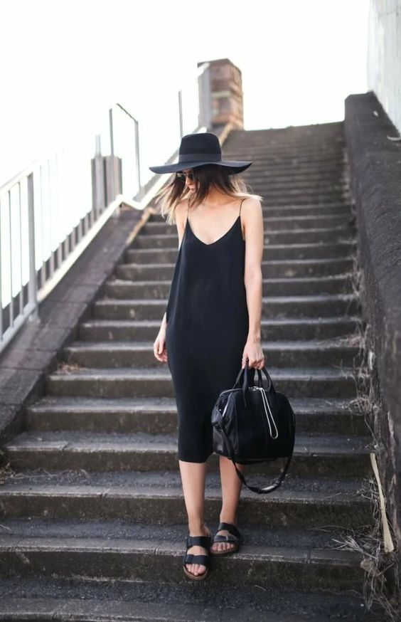 a black slip midi dress, black birkenstocks, a bag and a hat for a chic and bold summer look