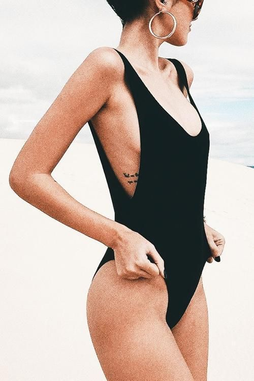 a black solid swimsuit with cutout sides, a deep neckline and a high cut bottom for a 90s inspired look