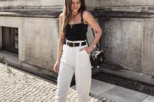 a black spaghetti strap top, white cropped pants, black mules and a black bag for a chic and cool hot day look