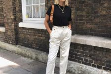 a black t-shirt, white high waisted pants, black strappy shoes and a brown saddle bag for summer