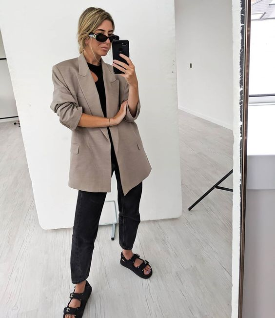 a black top, black jeans, black jeans, a grey oversized blazer for a trendy and bold summer work outfit