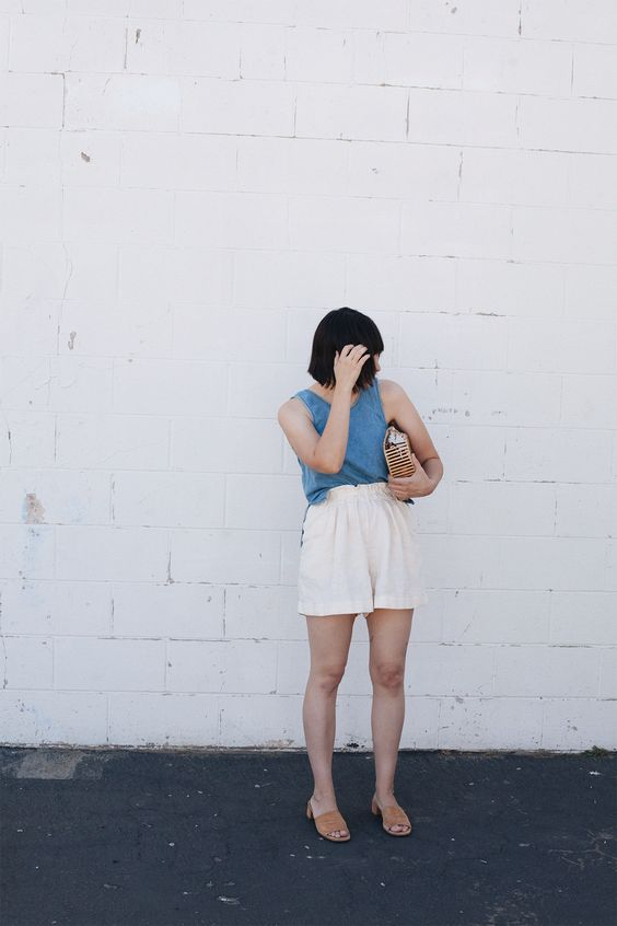 a blue linen top, neutral linen shorts, nude mules, a wooden bag are all you need in a heat wave