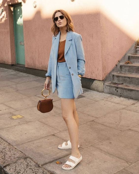 a blue skirt suit with a rust-colored top and a matching bag, white birkenstocks for an elegant professional look