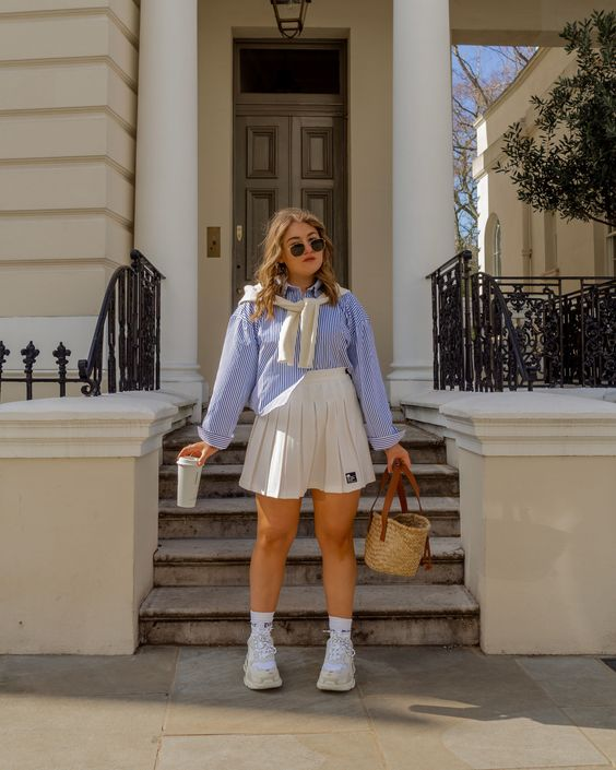 a blue striped shirt, a white high waisted pleated mini, white socks and trainers plus a straw bag for a comfy look